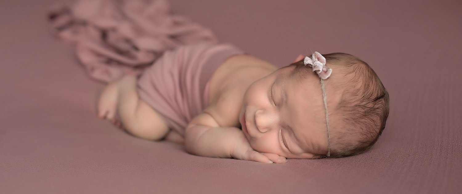 Sleeping newborn with pink background